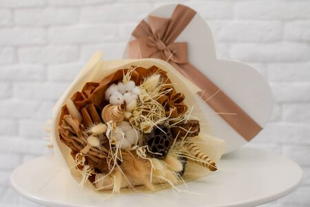 Decorative bouquet of dried plants in package on table. spikelets of flowers.