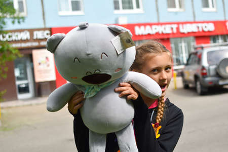 Teenager girl with soft cute toy near the store rejoices.