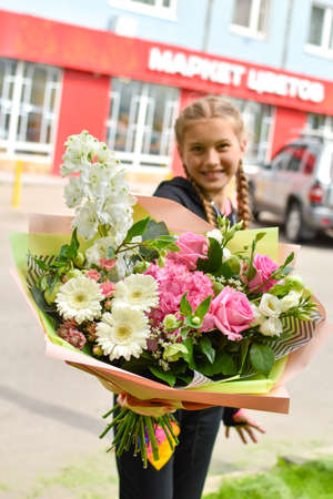 Girl child gives flowers. Women's Day. Teenage with flowers outside a store