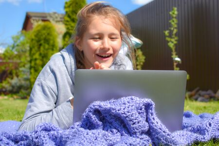 Happy little teen girl on a blanket outside looking at a laptop