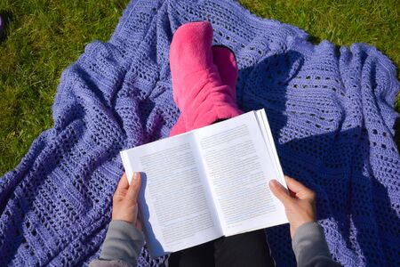 Girl reading a book on the grass. Distance learning outdoor