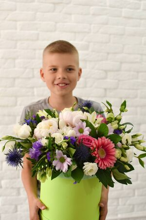 A floral gift for mom or teacher. boy with flowers.