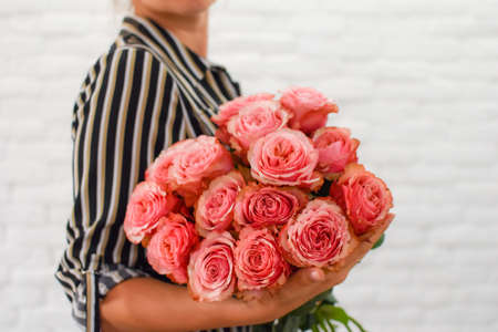a young girl with pleasure holds in her hands pink peonies bouquet.