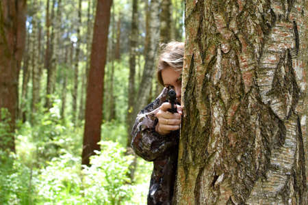 woman with a hand gun in forest shoots at a target. Archivio Fotografico