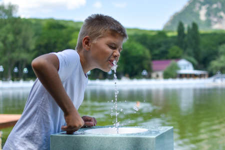 boy drinks clean water from a fountain. Fountain with spring mineral water in resort.
