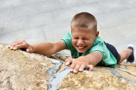 child falls off a cliff. danger of falling from hill. climb high mountain. child fear