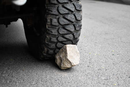 stone under the wheel of car. wheel chock. parking on mountain. danger of rolling off vehicle