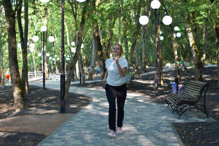 sports girl runs in the park in summer, morning wellness jogging, outdoor sports