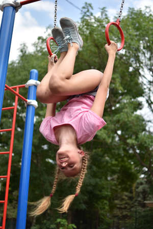Child girl on outdoor athletic rings. outdoor. Child teenager girl goes in for sports on the street on the playground.