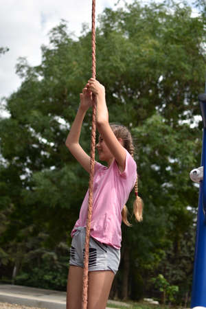 Child girl on a sports rope hanging outdoor. Child teenager girl goes in for sports on the street on the playground.