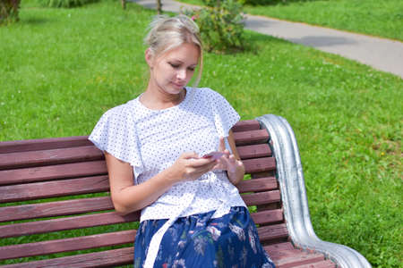 beautiful young blonde woman sits on outdoor bench with phone communicates online. Stylish natural female beauty. Fun positive web communication