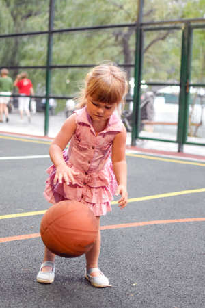 Little girl with a ball on sports field. Child with a big basketball on the playing field. Cute child playing basketball. sporty healthy baby