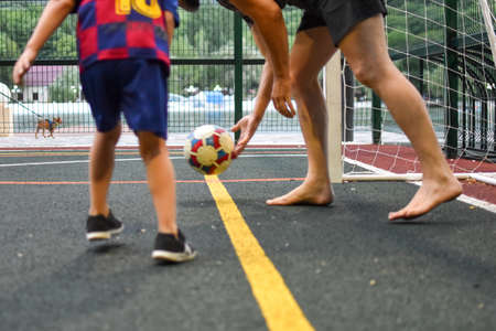 boy plays football with father on outdoor playing field. children's sport hobby with a ball. the child is practicing playing football