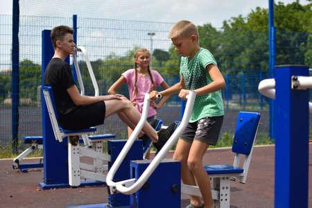 Children teenagers on sports playground. Active children on sports simulator outdoor. Healthy lifestyle for children.
