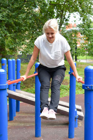 woman in park is engaged in gymnastics. girl on horizontal bar does outdoor exercise. active sports activities for health in nature Standard-Bild