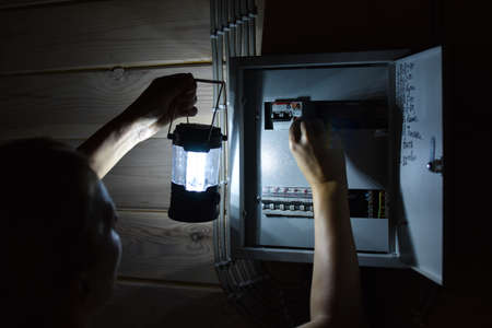 electrical panel with power buttons in house. In evening lights turned off. Woman looking for a problem in breaker panel