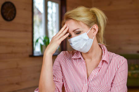 Sad tired young woman in medical mask at home in room. Stay home in quarantine. Lonely person in white protective mask on face.