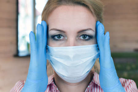 Portrait of caucasian woman in medical mask and blue gloves close-up. Home quarantine, protection against coronavirus.