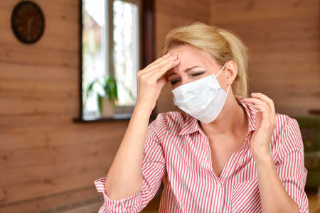 first symptoms of coronavirus. Headache in woman. woman in medical mask holds head. Head migraine with ARVI and flu. Virus protection measures. Standard-Bild