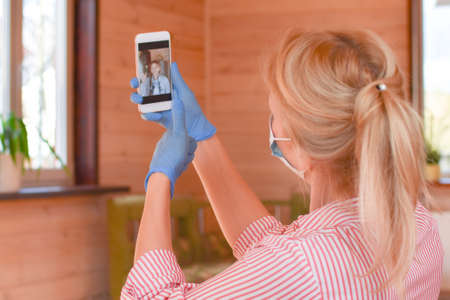 woman in medical mask and gloves is holding phone. Online communication from home. infectious patient sits at home on isolation. woman is talking on webcam on smartphone remotely.