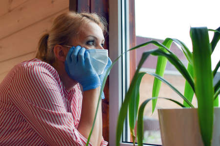 woman in medical mask and gloves looks out window. sad sick person. infectious patient sits at home on isolation. woman in mask on face looks longingly on street. Stay at home.