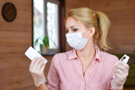 Woman in medical mask and gloves with medicines drugs. medical person is holding tablets from virus. woman treated at home for pneumonia. first measures to protect against virus. Pill or spray