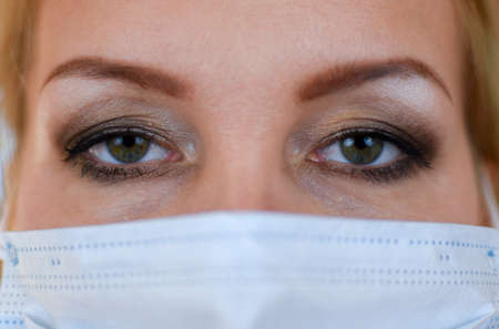 Woman in medical mask and gloves close up. Medical person with mask on face. woman is being treated at home for pneumonia. observe virus protection measures. stay at home Standard-Bild