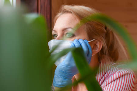 woman in a medical mask at home looks out window. Medical person sad with hope thinks. stay at home. self-isolation in house. girl sick patient in quarantine