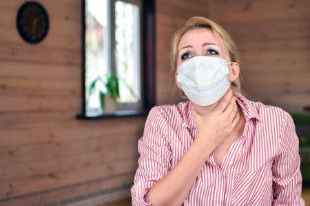 woman in medical mask is coughing at home. Medical person with fits of suffocating cough. observe virus protection measures. stay at home. symptoms of pneumonia. chest pain Standard-Bild