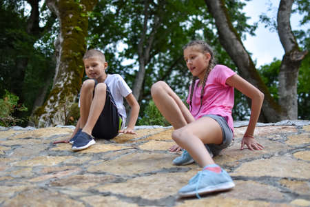friendly kids brother and sister crawl uphill, hang on high stone wall. fun adventures for children in nature. life of active healthy children. children looking for adventure outside