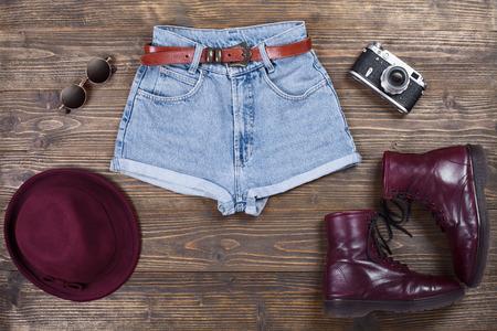 style: Fashion set di abiti a vita bassa e accessori per la donna su uno sfondo di legno.