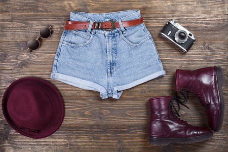 casual fashion: Fashion set of hipster clothes and accessories for woman on a wooden background.