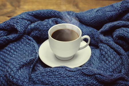 cold beverages: Cup of coffee on the warm blue knitted sweater background. Toned style instagram filters