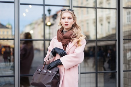 Street fashion concept: portrait of young beautiful woman wearing pink coat with handbag posing at the glass door. City lifestyle. Beautiful reflection background. Waist up Stock Photo