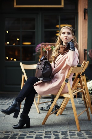 street cafe: Beautiful stylish young woman sitting in street cafe . City lifestyle. Female fashion. Full body portrait. Stock Photo