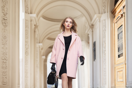 old architecture: Street fashion concept: portrait of young beautiful woman wearing pink coat with handbag walking in the city. Model looking at camera. Old architecture background.