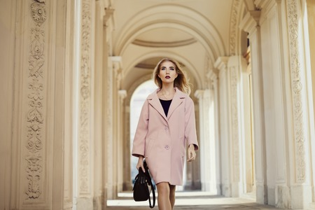 old architecture: Street fashion concept: portrait of young beautiful woman wearing pink coat with handbag walking in the city. Old architecture background. Stock Photo