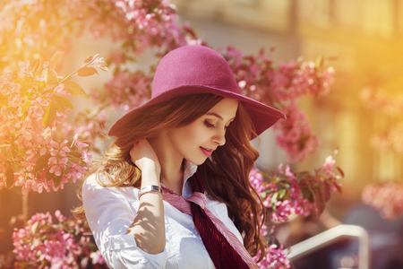 Outdoor portrait of young beautiful happy smiling lady posing near flowering tree. Model wearing stylish accessories and clothes. Girl closed her eyes. Female beauty and fashion concept. City lifestyle
