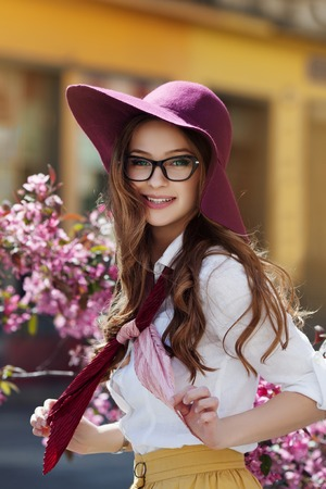 Outdoor portrait of young beautiful happy smiling lady posing near flowering tree. Model wearing stylish clothes. Girl looking at camera. Sunny day. Female beauty and fashion concept. City lifestyle