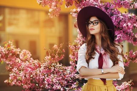 Retrato al aire libre de la señora de moda hermosa joven que presenta cerca de árbol floreciente. Modelo vistiendo accesorios elegantes y ropa. Chica mirando a un lado. Belleza femenina, concepto de moda. Estilo de vida de la ciudad Copia espacio para texto