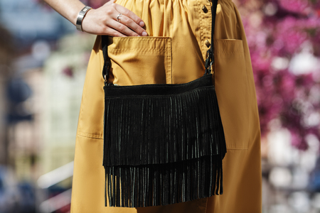 Elegant outfit. Closeup of the small black suede bag with fringe. Boho style. Fashionable girl on the street. Female fashion. City lifestyle.