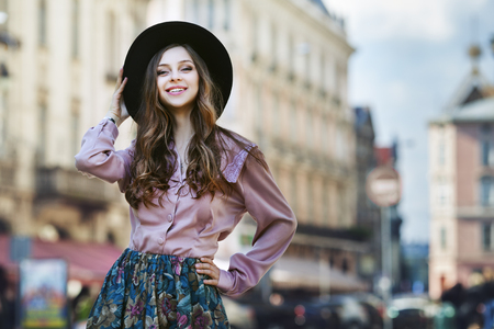 Outdoor portrait of a young beautiful fashionable happy lady posing on a street of the old city. Model wearing stylish clothes. Girl looking at camera. Female fashion. City lifestyle. Copy space.