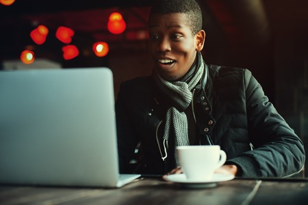 lap top: Indoor portrait of young black man sitting in cafe, drinking coffee or tea and working with lap top. Model looking at screen. Toned.