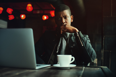 Indoor portrait of young black man sitting in cafe, drinking coffee or tea and working with lap top. Model looking at camera. Toned. Stock Photo