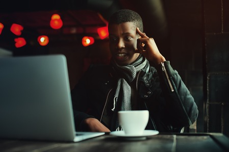 lap top: Indoor portrait of young black man sitting in cafe, drinking coffee or tea and working with lap top. Model looking at screen, expressing joyful and excitement with face. Toned. Stock Photo