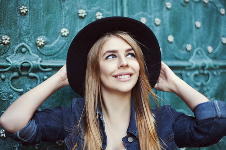 Street fashion portrait of a beautiful young lady smiling and looking up. Model wearing stylish wide-brimmed hat. City lifestyle.