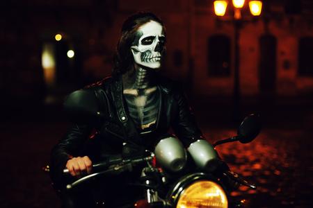 Mujer joven con maquillaje de Halloween que se sienta en la moto. Retrato de la calle. Cintura para arriba. Fondo de la noche de la ciudad