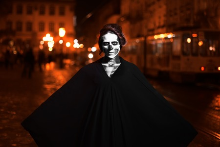 Young woman posing on the street in black costume with Halloween makeup . Waist up. Night city background. Stock Photo
