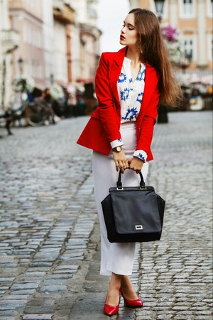 Female fashion concept. Outdoor full body portrait of a young beautiful confident fashionable business woman posing on the street. Model wearing stylish clothes. Girl looking aside. City lifestyle