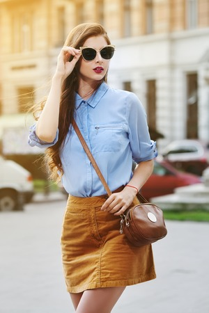 mini purse: Female fashion concept. Outdoor portrait of young beautiful confident lady walking on the street. Model wearing stylish clothes and sunglasses. Girl looking aside. Sunny day. City lifestyle. Waist up Stock Photo